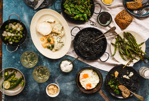 Rich vegetarian dinner with black pasta, grilled green vegetables, cheese and fried eggs over blue table.  - 124468159
