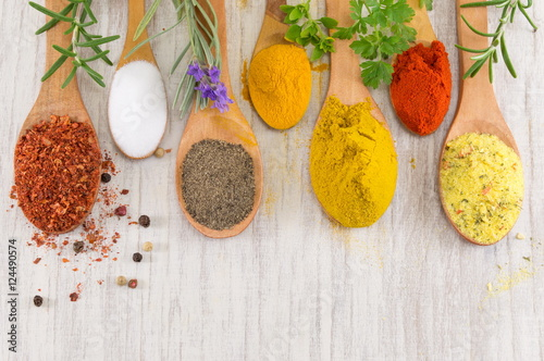 Various spices in wooden spoons on wooden table Poster