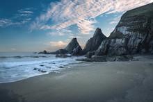 Erstaunlicher bunter Sonnenuntergang über Strand Landschaft mit schroffen Felsen f