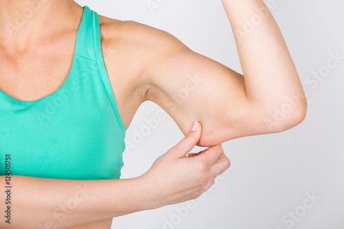 Poster junge Frau zieht an Haut am Ellenbogen