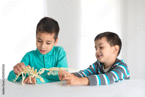 Poster boys  play with toys skeletons of dinosaurs