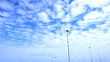 Fluffy clouds in the blue sky and the light pole lined
