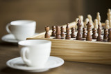Chess board game with two coffee cups beside