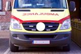 Moderner belgischer Krankenwagen oder Rettungswagen in den Farben Gelb und Rot parkend auf Parkplatz