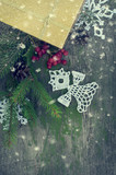 Christmas presents and white knitted snowflakes and angel on a rustic wood background with toning