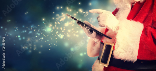 Santa Claus using tablet in snowy night