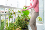 Charming Young Asian Woman Watering Plant In Container On Balcon - 124591179