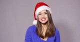 Happy glamorous young brunette woman in a festive red Santa Claus hat standing with folded arms smiling happily at the camera as she celebrates Christmas