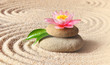 Spa stones with flower lily on sand.
