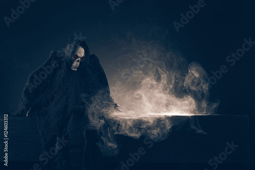Death sitting on the table on dark background Poster