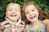 Above view portrait of two happy smiling kids lying on green grass. - 124622917