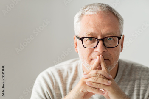 close up of senior man in glasses thinking