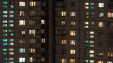 Windows lights in multistorey panel apartment house at night. Old building with cracks on the walls. Moscow, Russia