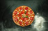 Raw pizza margarita on dark table