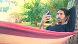 Young adult man using smartphone in his hammock