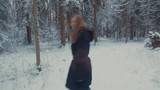 Girl running in the winter forest. She turns, whirls and throws snow
