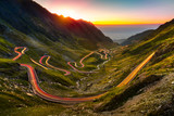 Traffic trails on Transfagarasan pass at sunset. Crossing Carpathian mountains in Romania, Transfagarasan is one of the most spectacular mountain roads in the world. - 124679927