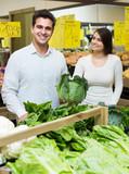 spouses choosing veggies in store