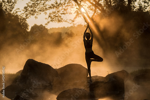 Fototapeta Young woman practice yoga in a hot spring