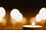 Burning candle against golden candlelight background