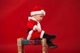 cute kid in Santa Claus clothes. sitting on a chair