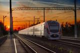 Passenger między miastami pociągu w mieście na tle zachodu słońca