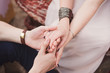 Closeup of a couple holding hands, girl wearing an engagement ring with blue jem on her finger. Shallow focus.