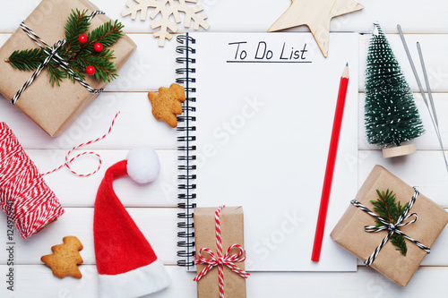 Holiday decorations, gift, present box, miniature fir tree and notebook with to do list on white wooden table from above Poster