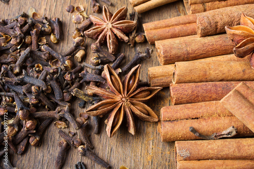 cinnamon sticks, star anise and cloves on wooden background