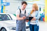 Kfz-Werkstatt Mechaniker übergibt Auto mit Protokoll an Kundin