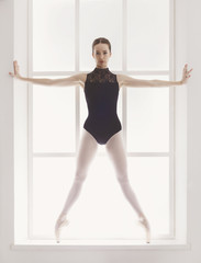 Beautiful ballerine stands in releve ballet position