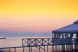 pergola veranda on stilts on the beach at dawn. Beautiful sky and the sun rising from the horizon. Natural marine species.