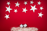 Christmas background - white stars over a red background with silver angel-hair and xmas-gifts - 125090798