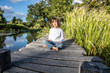 relaxed child for yoga and meditation near water and trees