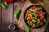 Hot spicy stew eggplant, sweet pepper, olives and capers with basil leaves. Top view - 125133986
