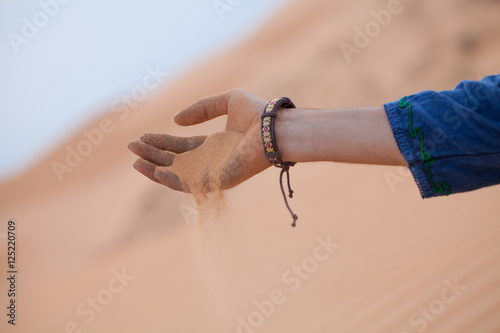 Single hand holding sand in desert let it running through fingers, Muine sand du Poster