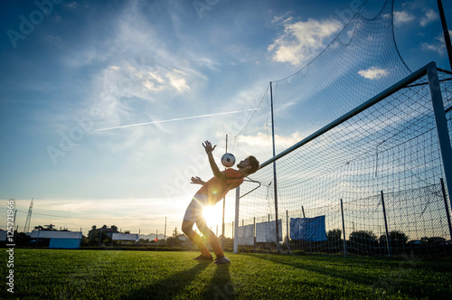 Football player is training at the field on a sunset background