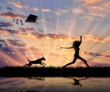Girl with a dog running with a kite