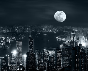 Night aerial view panorama of Hong Kong skyline at full moon night under cloudy sky