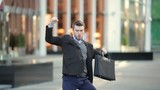 Attractive man with a beard and briefcase dancing in the street