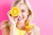Happy young woman holding orange halves
