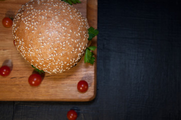 Delicious fresh hamburger on a chopping board and cherry tomatoe