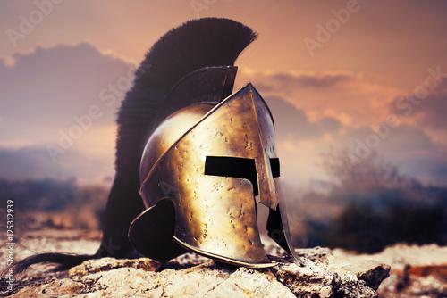 Spartan helmet on ruins with sunset sky.