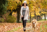 Happy woman walking her Golden Retriever Dog in a park with Fall - 125321364
