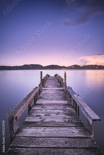 Fotobehang Pier Wooden pier or jetty on a blue lake sunset. Italy