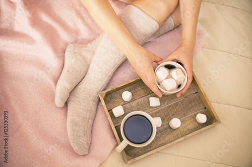Papiers peints Chocolat coffee in bed. shapely female legs in warm socks, wooden tray for breakfast in bed. two cups of coffee and marshmallows. the concept of cozy home. top view