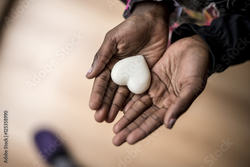 African-American girl hands holding a marble made heart