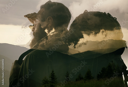 Closeup photo of stylish bearded traveler looking into the distance. Double exposure, beautiful mountain landscape background. Made in vintage style. - 125360102