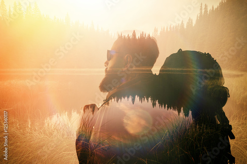 Portrait of stylish bearded man with glasses and tourism backpack.  Double exposure, view on  the beautiful mountain lake. Wide, sunset effect. - 125360117