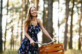 Happy girl on a bicycle with a basket in the woods.